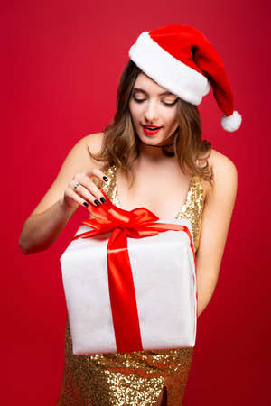 Beautiful sexy Santa girl in a gold elegant evening dress and Christmas hat with a New Year gift in hands. Guess whats inside the box