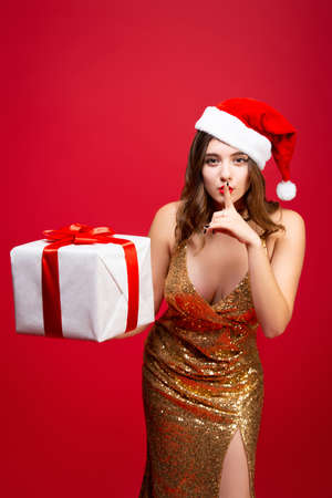 Beautiful sexy Santa girl in a gold elegant evening dress and Christmas hat with a New Year gift in hands. Shhh, secretly, dont tell anyone Stock Photo - 152103559