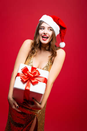 Beautiful sexy Santa girl in gold elegant evening dress and Christmas hat with a New Year gift in hands. Emotions happiness and delight. Smiling face Stock Photo