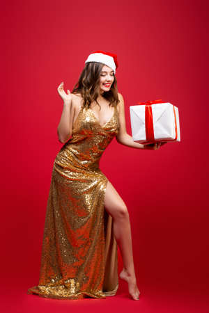 Beautiful sexy Santa girl in gold elegant evening dress and Christmas hat with a New Year gift in hands. Emotion of surprise on the face. Try to guess