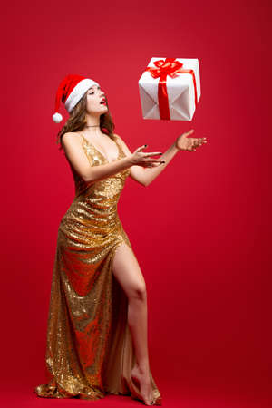 Beautiful sexy Santa girl in a gold elegant evening dress and Christmas hat with a New Year gift in hands. Throws the box up