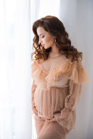 A beautiful pregnant young woman stands in a beige vintage dress near a white lace screen and touches the tummy with a baby.