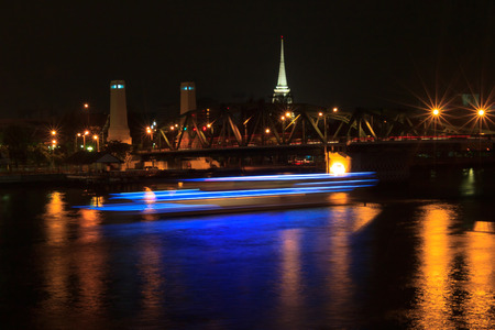 Memorial Bridge in Bangkok, Thailand at night with a boat passing by photo