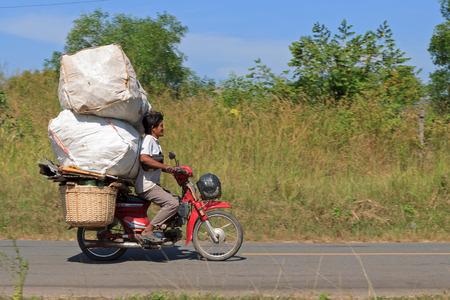 SIHANOUKVILLE, CAMBODIA - NOVEMBER 18, 2014 Unidentified man drives overloaded motorcycle in Sihanoukville, Cambodia