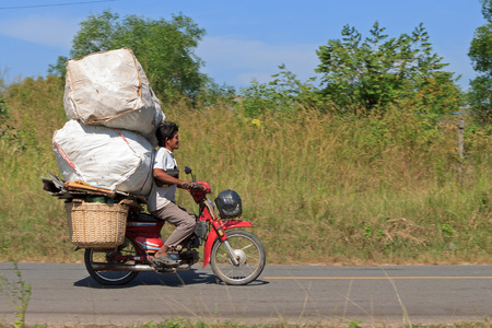 SIHANOUKVILLE, CAMBODIA - NOVEMBER 18, 2014 Unidentified man drives overloaded motorcycle in Sihanoukville, Cambodia