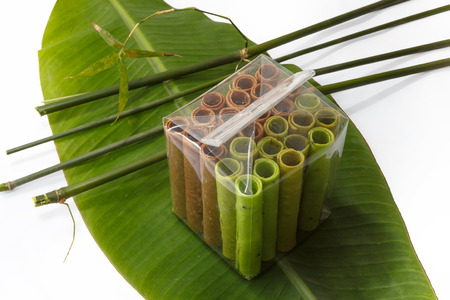 Colorful waffle rolls packed in transparent plastic bag on a leaf with bamboo sticks photo