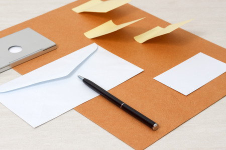 notelet: A set of blank envelopes, sticky notes, business card and pen side view