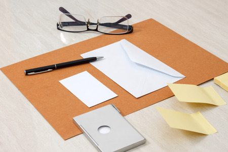 A set of blank envelopes with paper, pen, glasses, business card ans sticky notes side view photo