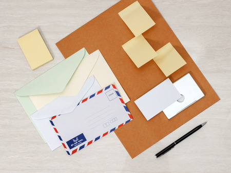 A set of blank envelopes different size, sticky notes, business card and pen photo