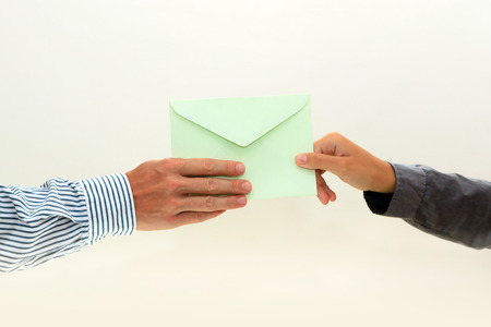 womans hand passes a green envelope to male hand on white background view 1 Reklamní fotografie