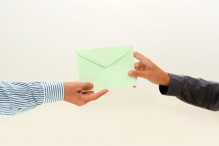 letter envelopes: pasa a mano de la mujer un sobre verde a mano masculina en el fondo blanco Vista 2
