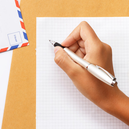 write letter: Female hand writing a letter on paper with envelope on the table view 2 Stock Photo