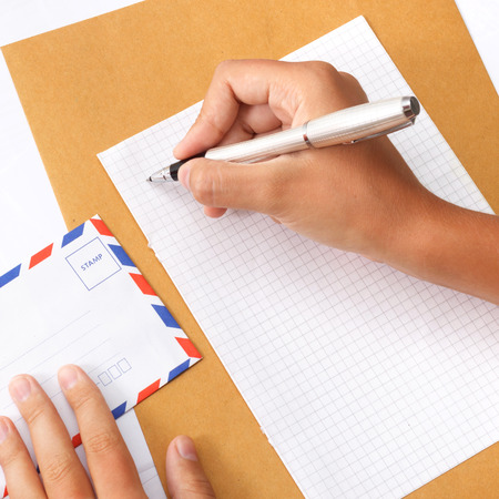 Female hand writing a letter on paper holding envelope photo