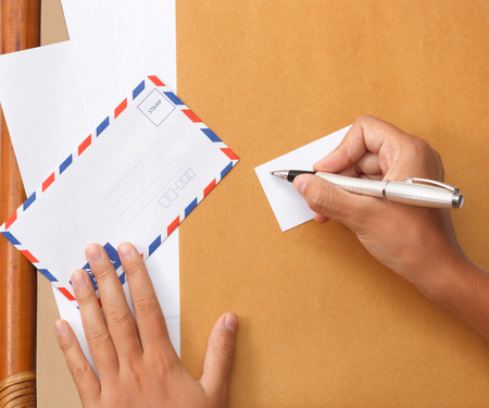 Female hand writing a note on business card holding envelope photo