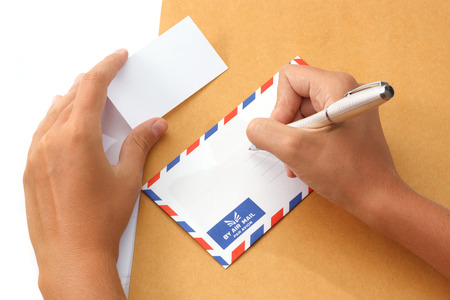 Female hand writing address on envelope holding a business card photo