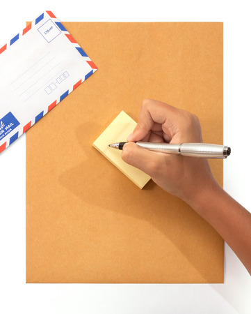 Female hand writing a note on sticky notes with envelopes on background photo