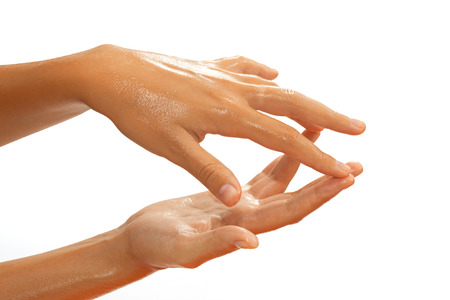 Close-up of female hands while applying oil on white background view 5 Stock Photo