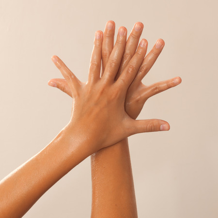Golden tinted photo of female hands in oil on beige background view 2 Stock Photo