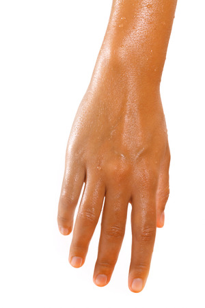 Close-up of female hand in oil on white background