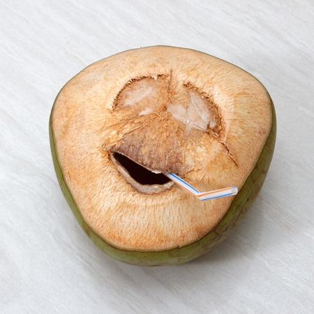 drinking water sign: Fresh green young coconut with cut out grin face and straw on wooden background view 2