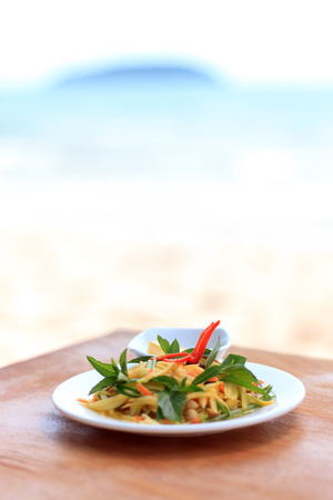Natural light photo with shallow DOF of spicy green mango salad on a wooden table with a sea view on the background photo