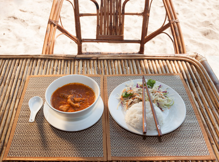 amok: Natural light photo with shallow DOF of traditional Cambodian a-mok coconut curry with steamed rice and salad on a wooden table horizontal view