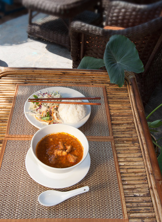 amok: Natural light photo with shallow DOF of traditional Cambodian a-mok coconut curry with steamed rice and salad on a wooden table side view