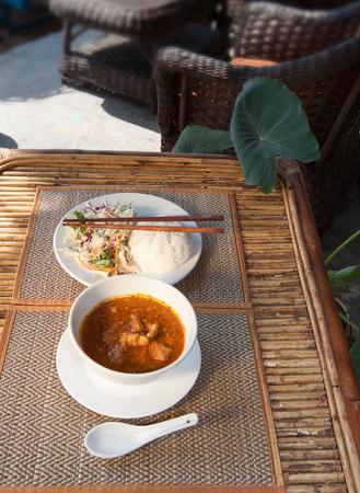 amok: Naturalne zdjęcie światło z płytkie DOF tradycyjnej Kambodży-mok kokosowym curry z ryżem i sałatką na drewnianym stole boku Zdjęcie Seryjne