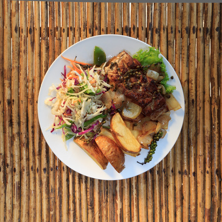 cambodian: Natural light photo of Cambodian barracuda steak with french fries and salad on a wooden table top view