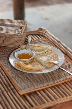 rattan mat: Natural light photo with shallow DOF of crepes with mango jam, tableware and rattan napkin holder on mat and a wooden table view 1