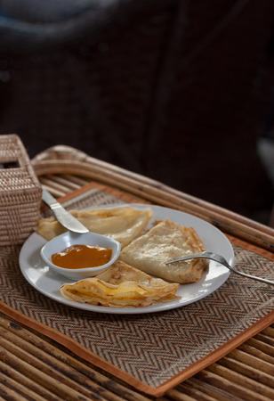 rattan mat: Natural light photo with shallow DOF of crepes with mango jam, tableware and rattan napkin holder on mat and a wooden table view 2