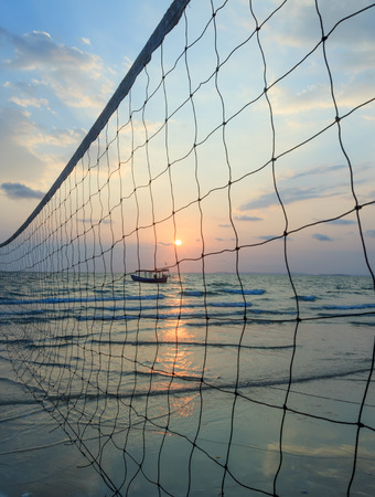 sillhouette: Sillhouette of a volleyball net against sunset on the beach with boat on horizon