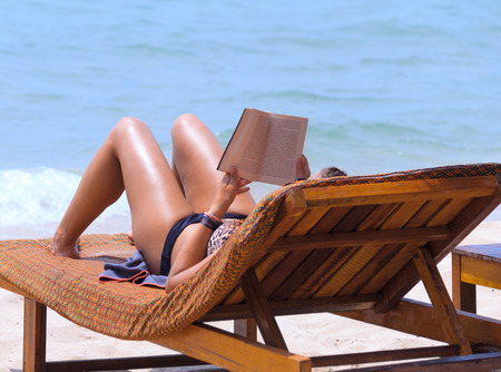 beach mat: Woman reading book on chaise longue at the seaside
