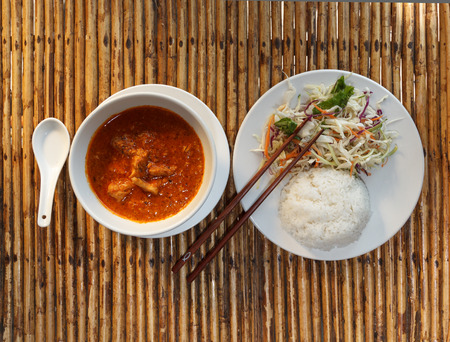 Natural light photo of traditional Cambodian a-mok coconut curry with steamed rice and salad on a wooden table top view