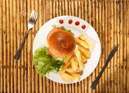 sandwich de pollo: Foto La luz natural de hamburguesa de pollo y papas fritas en un plato con vista superior vajilla