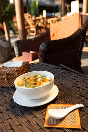 Natural light photo of asian vegetable and mushrooms soup with napkin holder.    photo