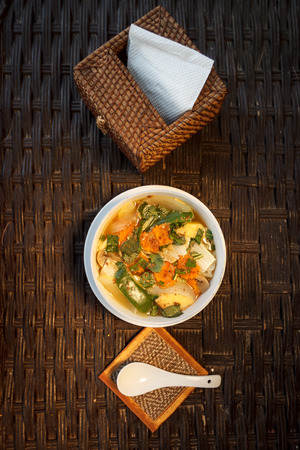 Natural light photo of asian vegetable and mushrooms soup with napkin holder top view photo