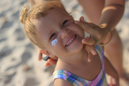 Cute baby girl applying sun screen lotion for safe tan and skin care view 1 Stockfoto