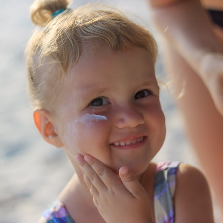 Cute baby girl applying sun screen lotion for safe tan and skin care view 2 photo