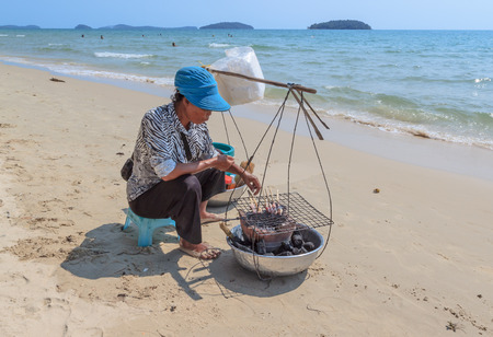 hard sell: SIHANOUKVILLE, CAMBODIA -  MARCH 05, 2015: unidentified woman seller seafood on a beach