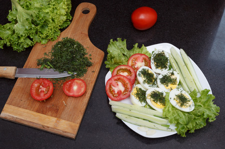 Assorted vegetables and eggs with a chopping board and a knife on granite surface top view photo