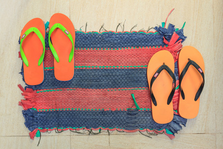 welcome mat: Colorful asian floor mat with flip flops on it Stock Photo