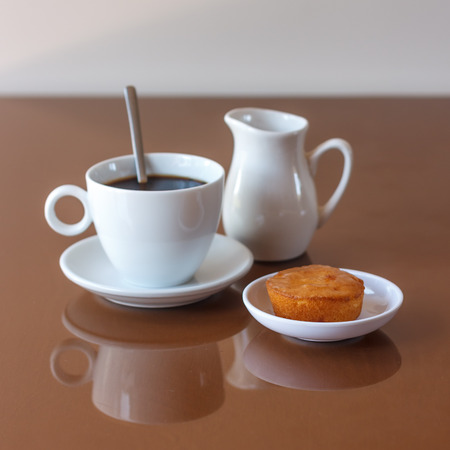 creamer: Cup of coffee, creamer jug and muffin on reflective table, view 1 Stock Photo