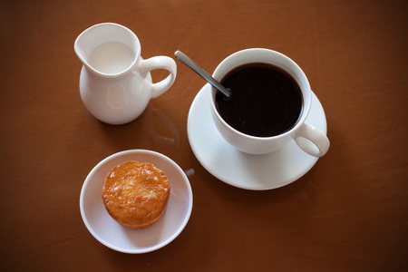creamer: Cup of coffee, creamer jug and muffin on reflective table, view 3