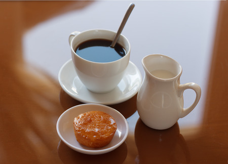 creamer: Cup of coffee, creamer jug and muffin on reflective table, view 2