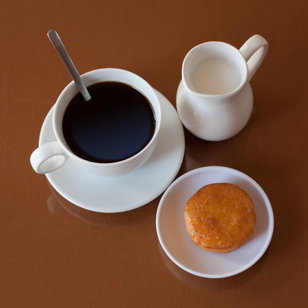 creamer: Cup of coffee, creamer jug and muffin on reflective table, top view Stock Photo