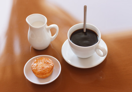 creamer: Cup of coffee, creamer jug and muffin on reflective table, view 4