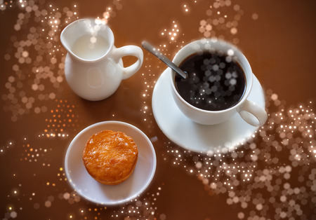 creamer: Cup of coffee, creamer jug and muffin on reflective table with glitter and flare special effect