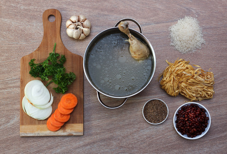 Chicken soup ingredients: broth in pan with fresh vegetables, red beans, yellow yolk noodles and salt, top view 3 Reklamní fotografie