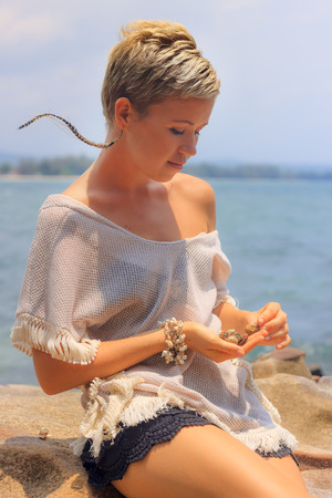 thin shell: Beautiful young woman sitting on picturesque rocky seashore playing with shells